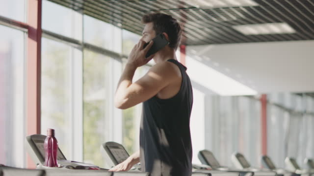 Handsome man using mobile phone in gym. Strong sportsman jogging on treadmill