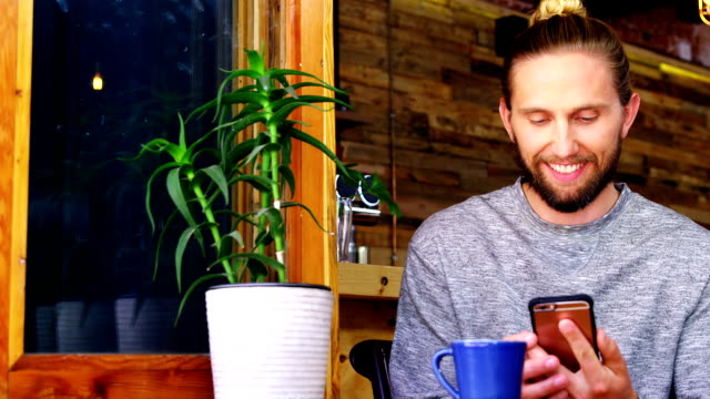 handsome man using mobile phone while having coffee - piattino video stock e b–roll