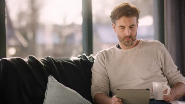 handsome man using tablet and drinking coffee - guy sofa video stock e b–roll