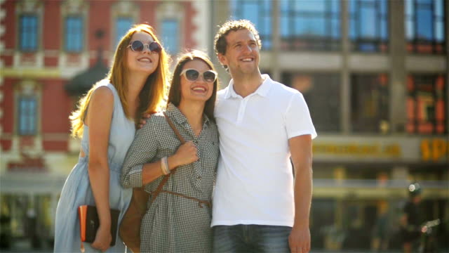 Handsome Man Wearing White Shirt is Standing at the Old City Square with Two Pretty Beatiful Girls in Fashionable Sunglasses and Dresses video