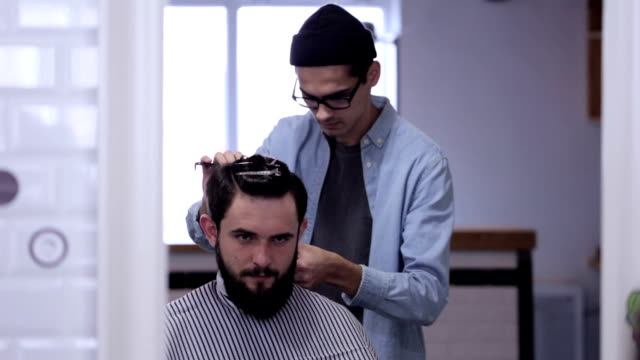 Handsome man with beard in barbershop. Barber working with electric razor. video