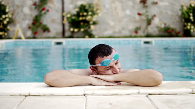 handsome man with googles enjoy luxury swimming pool side, cinematic dof - google filmów i materiałów b-roll
