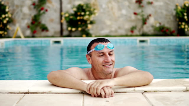 handsome man with googles relax luxury swimming pool side smiling to camera, cinematic dof - google filmów i materiałów b-roll