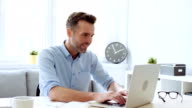 istock Handsome man working at home office on laptop 1159546229