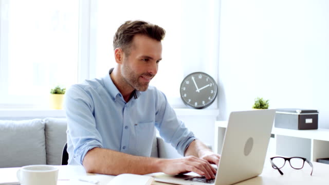 Handsome man working at home office on laptop
