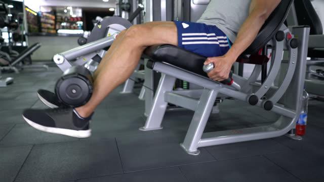 vídeos de stock e filmes b-roll de handsome man working out his legs on machine at the gym - aparelho de musculação