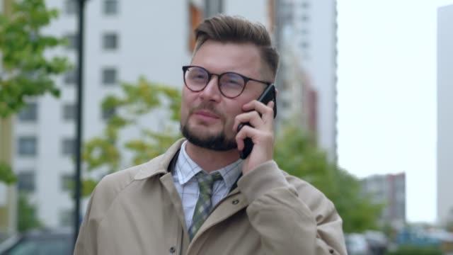 ハンサムなマネージャーをモバイルで会話を持って徒歩で朝の仕事を得ることを楽しんで豊かなビジネスマンは、良い気分で電話で話している所に歩いて。 - 電話を使う点の映像素材/bロール