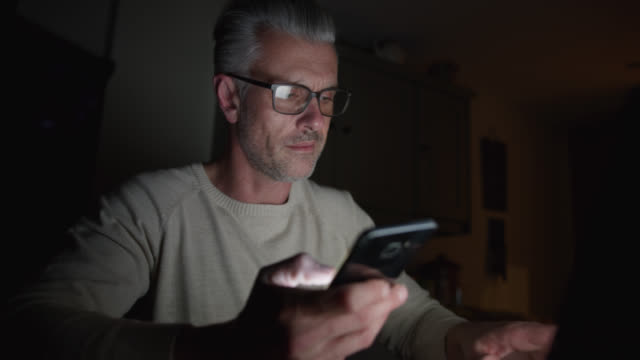 Handsome mature man at home working online using laptop and smartphone late at night
