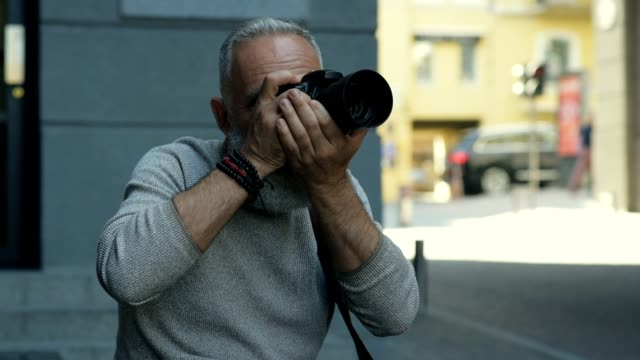 Handsome mature man smiling while photographing outdoors Capturing moments. Bearded man taking photos of a surrounded area while sitting in the street and smiling cheerfully. hobbies stock videos & royalty-free footage