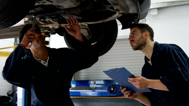 Handsome mechanics overhauling a car video
