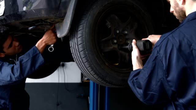 Handsome mechanics repairing a car video