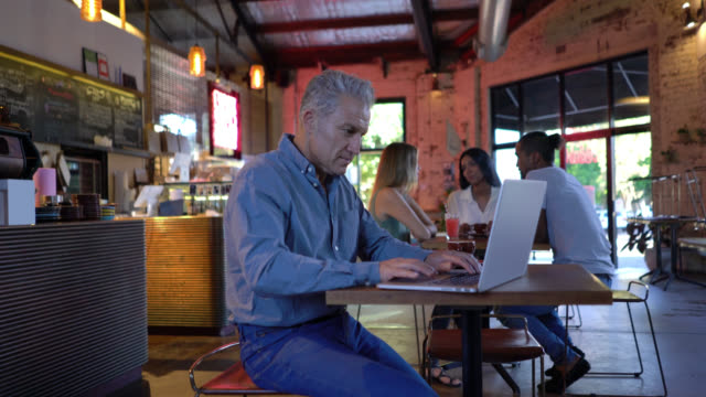 handsome mid adult man working on his laptop at a bakery looking very happy - caffetteria video stock e b–roll