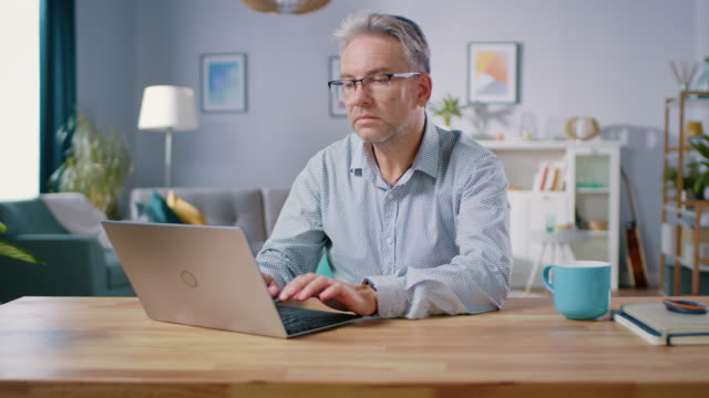 handsome middle aged man uses laptop computer while sitting at his desk in the cozy and stylish living room. happy successful man works on computer from home. - capelli grigi video stock e b–roll