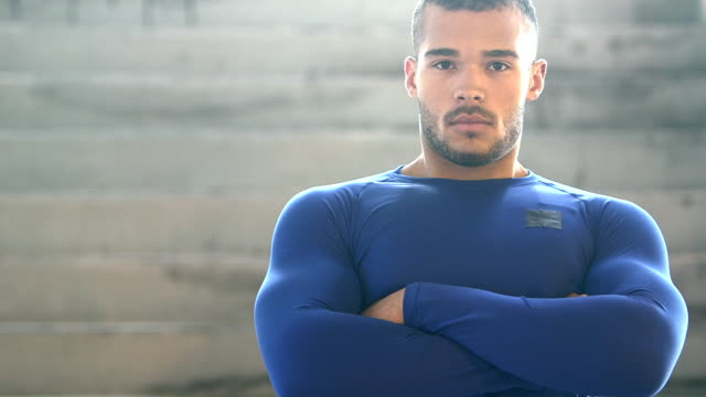 Handsome, muscular, mixed race young man, serious A handsome athlete staring at the camera, arms crossed. He is a mixed race African-American and Native American young man in his 20s with a very muscular build. physical position stock videos & royalty-free footage