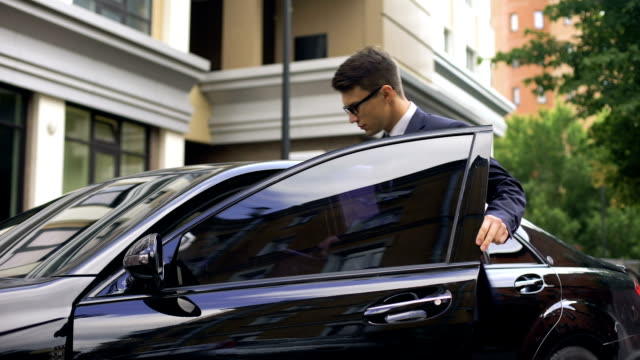 handsome office worker getting in new luxury car near business center, promotion - entrata video stock e b–roll