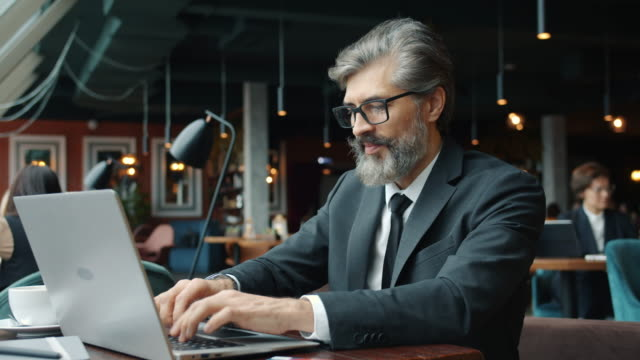 Handsome office worker in formalwear using laptop in cafe at table typing working alone video
