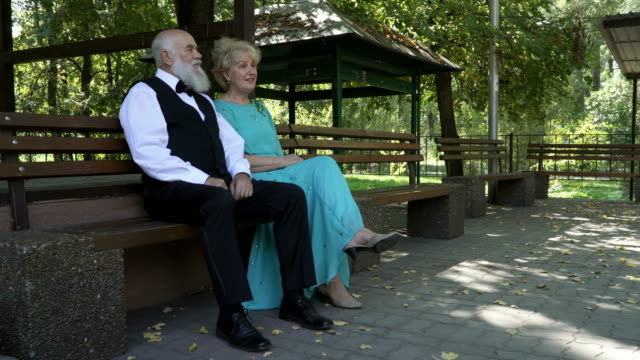 Handsome old man and pretty old woman resting on bench in park video