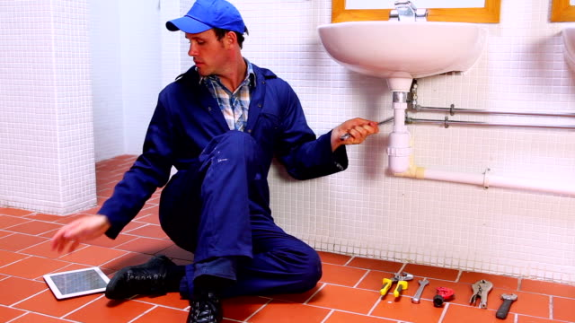 Handsome plumber fixing sink and checking tablet pc video