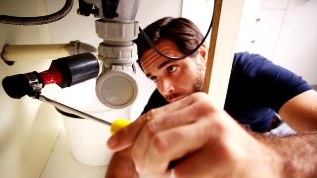 Handsome plumber using screwdriver to fix sink video