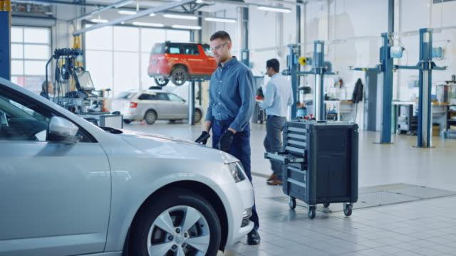 handsome professional car mechanic arbetar på ett fordon i en tjänst. happy repairman stänger huven. specialist är bär skyddsglasögon. han tittar på en kamera och leenden. - maskindel bildbanksvideor och videomaterial från bakom kulisserna