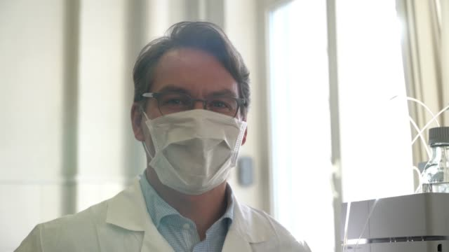 handsome professional scientist facing camera smiling and then putting on a protective mask - mask filmów i materiałów b-roll