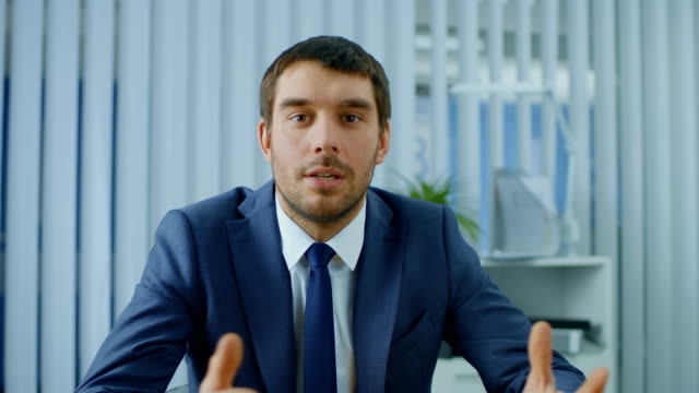 handsome respectable businessman sitting at his desk, talking into the camera, charismatically gesturing. - conference call stock videos & royalty-free footage