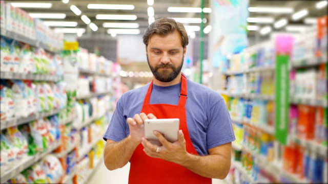handsome salesman using digital tablet standing among shelves in supermarket - struttura pubblica video stock e b–roll