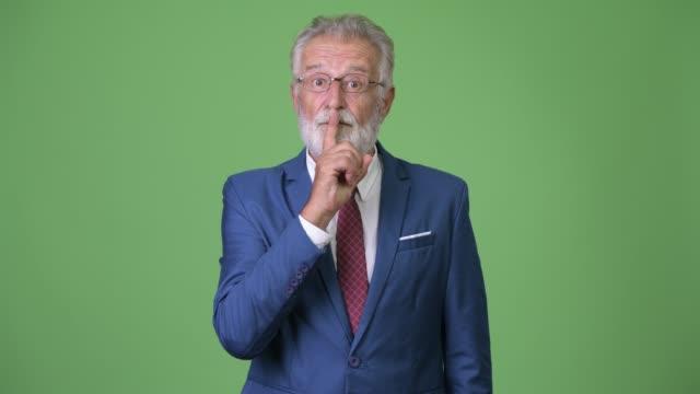 handsome senior bearded businessman against green background - cisza filmów i materiałów b-roll