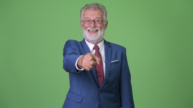Handsome senior bearded businessman against green background Studio shot of handsome senior bearded businessman against chroma key with green background pointing stock videos & royalty-free footage