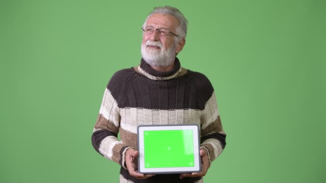 Handsome senior bearded man wearing warm clothing against green background video