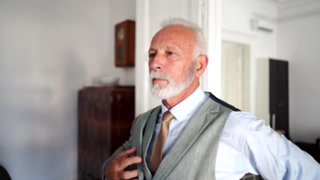 vídeos y material grabado en eventos de stock de apuesto hombre de negocios senior vestirse antes de ir a la oficina - bien vestido