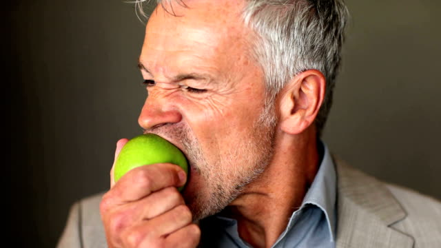 A handsome senior executive eating an apple on a dark background video