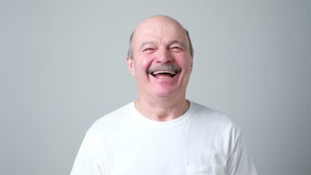 handsome senior man in white t-shirt laughing - maglietta bianca video stock e b–roll