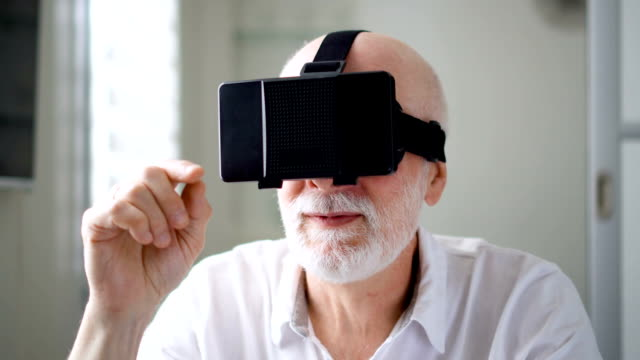 Handsome senior man in white using VR 360 glasses at home. Making browse, zoom and tap gestures video