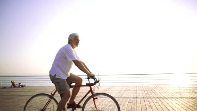 stilig senior man rider bike vid havet, slowmotion - active senior bildbanksvideor och videomaterial från bakom kulisserna