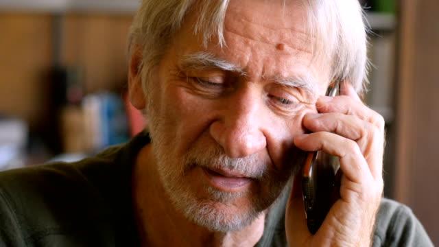 handsome senior man talking on smart phone mobile device in his house - rispondere video stock e b–roll