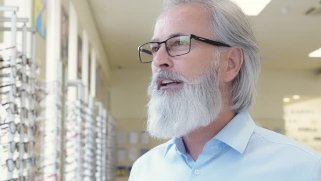 Handsome senior man trying on prescription glasses video