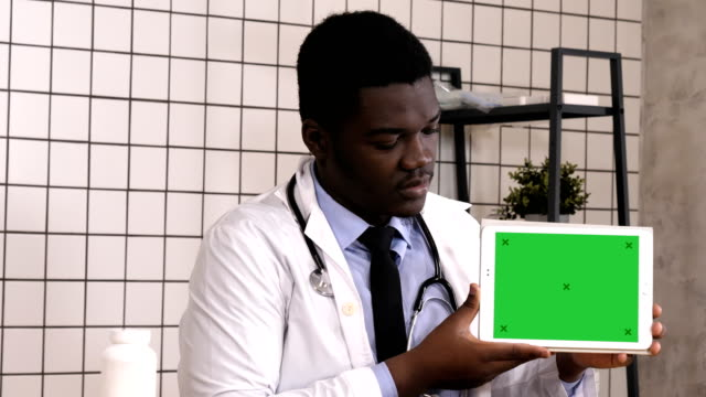 Handsome serious African doctor presenting product on tablet screen. White Display