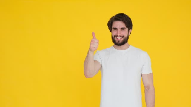 handsome smiling bearded young guy 20s in white t-shirt isolated on yellow background in studio. people sincere emotions, lifestyle concept. looking approvingly at camera showing thumbs up - maglietta bianca video stock e b–roll