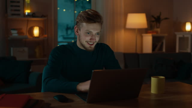 vídeos de stock e filmes b-roll de handsome smiling man works on a laptop while sitting at his desk at home, he does video call and talks with friends. cozy living room in the evening. - webinar anuncio