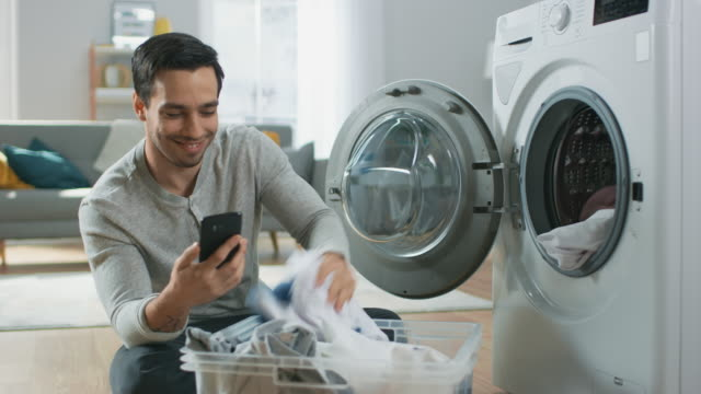 Handsome Smiling Young Man in Grey Jeans and Coat Sits in Front of a Washing Machine and Uses His Smartphone. He Loads the Washer with Dirty Laundry. Bright and Spacious Living Room with Modern Interior.