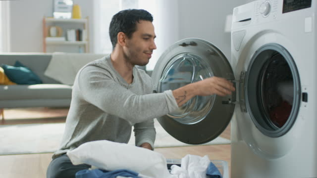 handsome smiling young man in grey jeans and shirt sits in front of a washing machine at home. he loads the washer with dirty laundry. bright and spacious living room with modern interior. - pranie filmów i materiałów b-roll