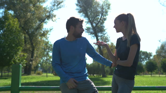 handsome sports people having a conversation while relaxing at a park - active lifestyle stock videos & royalty-free footage