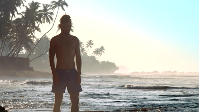 handsome sportsman stretches neck against ovean waves slow