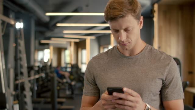 stockvideo's en b-roll-footage met knappe sportsman die bericht in sportclub sms'. bodybuilder die zich bij gymnastiek bevindt - call center