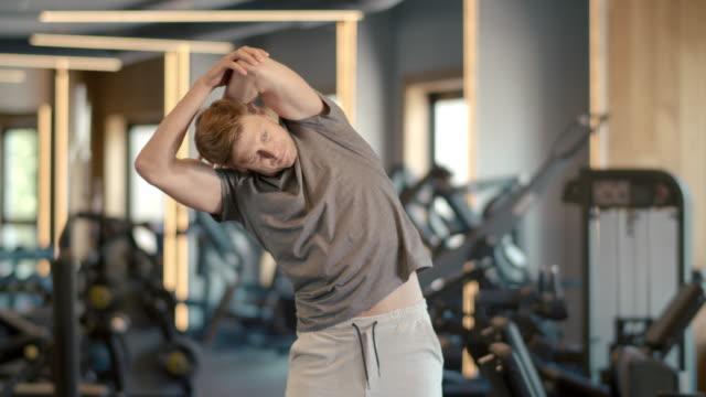 stilig idrottsman uppvärmning på gym. fitness man gör övningar i idrottsförening - människorygg bildbanksvideor och videomaterial från bakom kulisserna