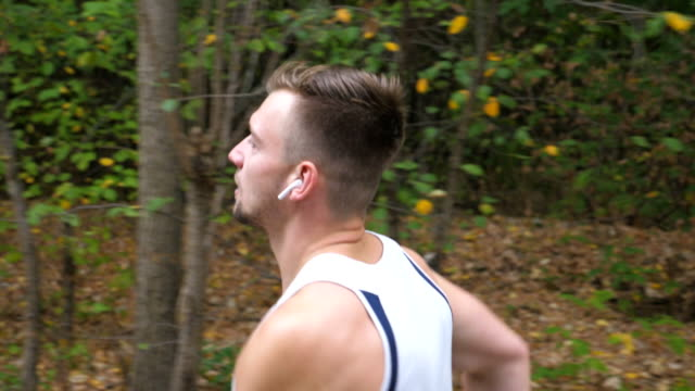 handsome sporty man sprinting fast along trail near forest at early autumn. young strong sportsman jogging outdoor. athletic guy with wireless headphones running at nature. healthy active lifestyle. - cuffie wireless video stock e b–roll