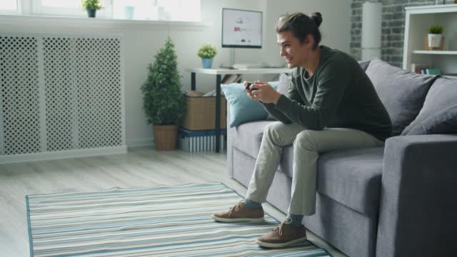vacker student spelar tv-spel i lägenhet ha kul med gadget - unga män bildbanksvideor och videomaterial från bakom kulisserna