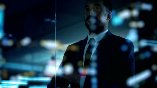 handsome suited businessman looks out of the office window at the big city in the night. successful man on the top of the world. - business people stock videos & royalty-free footage