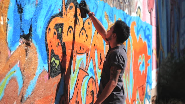 Handsome Talented Young Boy making a colorful graffiti with aerosol spray on urban street wall. Cinematic toned slow motion footage. Creative art. Gimbal shot. Side view video